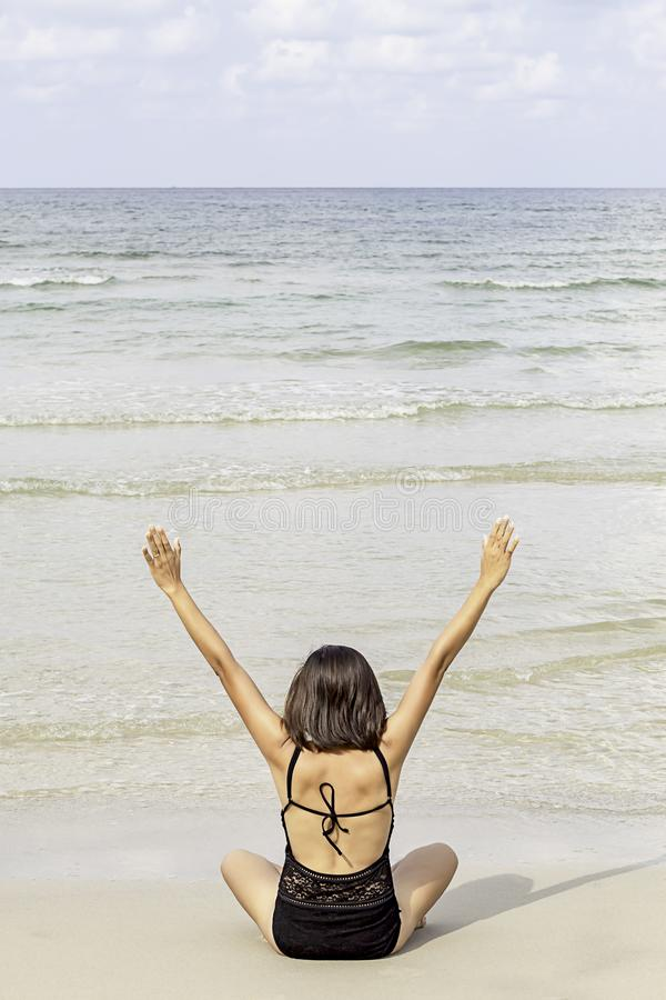 Portrait of Asian woman wearing a swimsuit sitting yoga on the beach background sea and sky stock photo