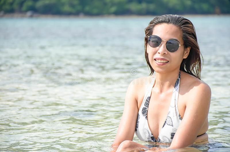 Portrait of Asian woman wearing white swimsuit and wear sunglasses lying on a sandy beach royalty free stock images