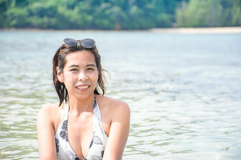 Portrait of Asian woman wearing white swimsuit and wear sunglasses lying on a sandy beach royalty free stock image