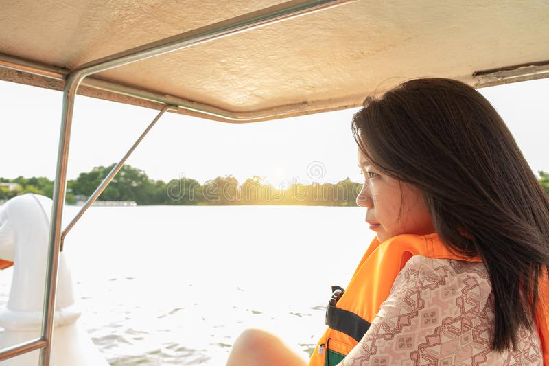 Portrait of asian women be abstracted in a boat bike. Portrait of asian woman be abstracted in a boat bike on the lake, there are green garden and sunset as stock photography