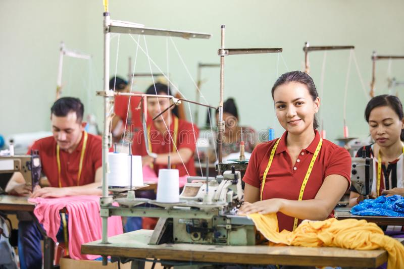 Asian workers in garment factory sewing with industrial sewing m. Portrait of asian workers in garment factory sewing with industrial sewing machine royalty free stock image