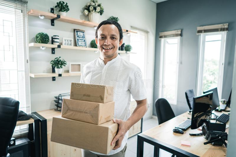 Portrait of asian young man carrying packages stock photography