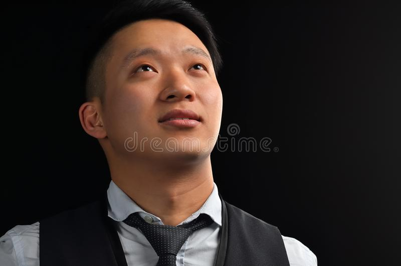 Portrait of an Asian young man looking up. Dressed in a shirt, smiling stock photo