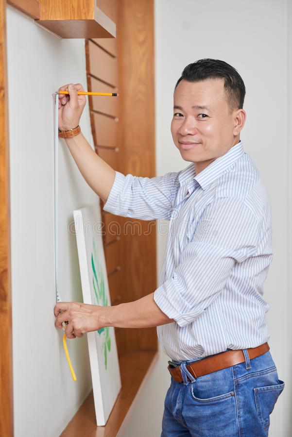 Man hanging the picture. Portrait of Asian young man measuring the wall with tape measure and preparing the place on the wall for the picture stock photography