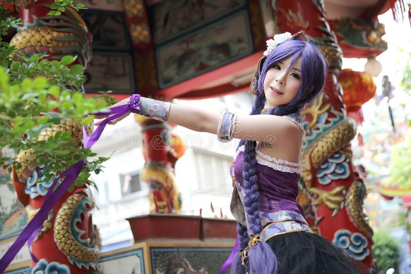 Portrait of asian young woman dancing with purple Chinese dress cosplay with temple. In close up royalty free stock photography