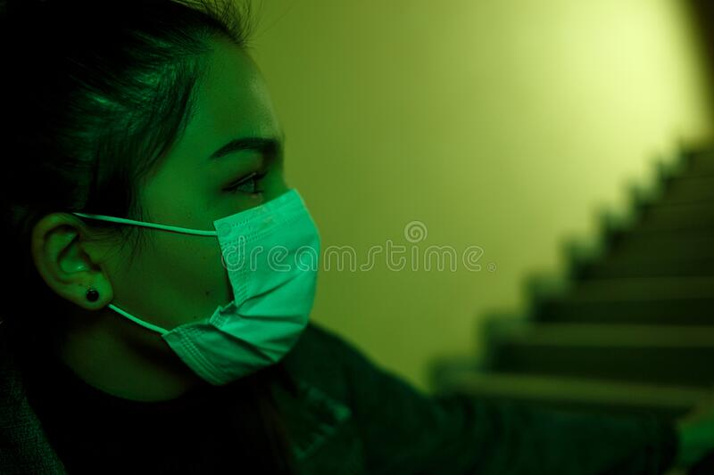 Portrait of an Asian young woman in a disposable medical mask. stairwell of the hospital. the girl looks back anxiously. fear royalty free stock photos