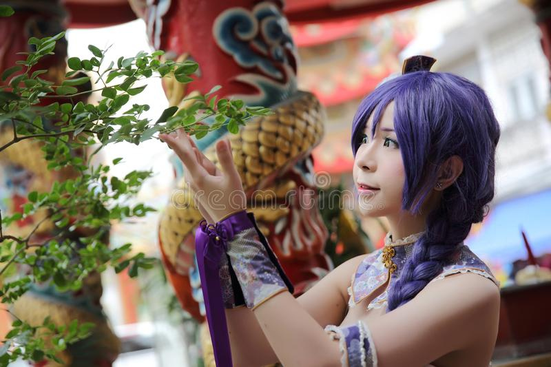 Portrait of asian young woman with purple Chinese dress cosplay with temple. Background royalty free stock image