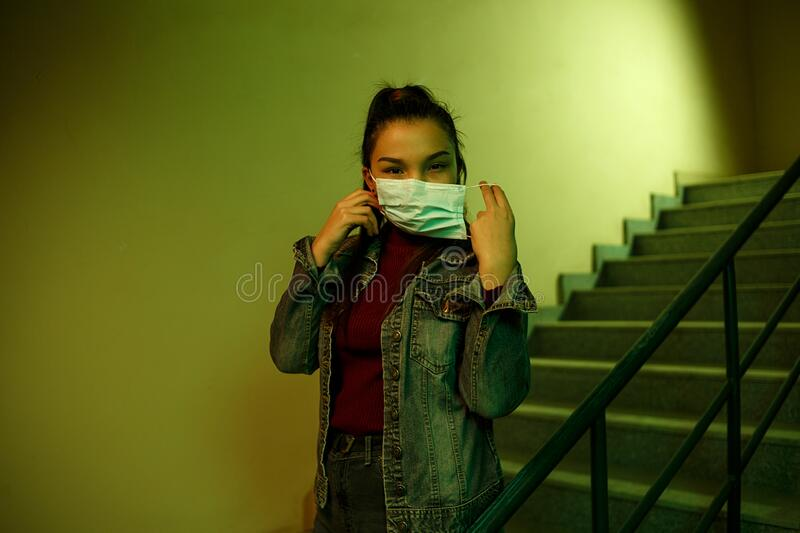 Portrait of an Asian young woman. stairwell of the hospital. the girl wears a mask to avoid getting infected with the virus stock photography