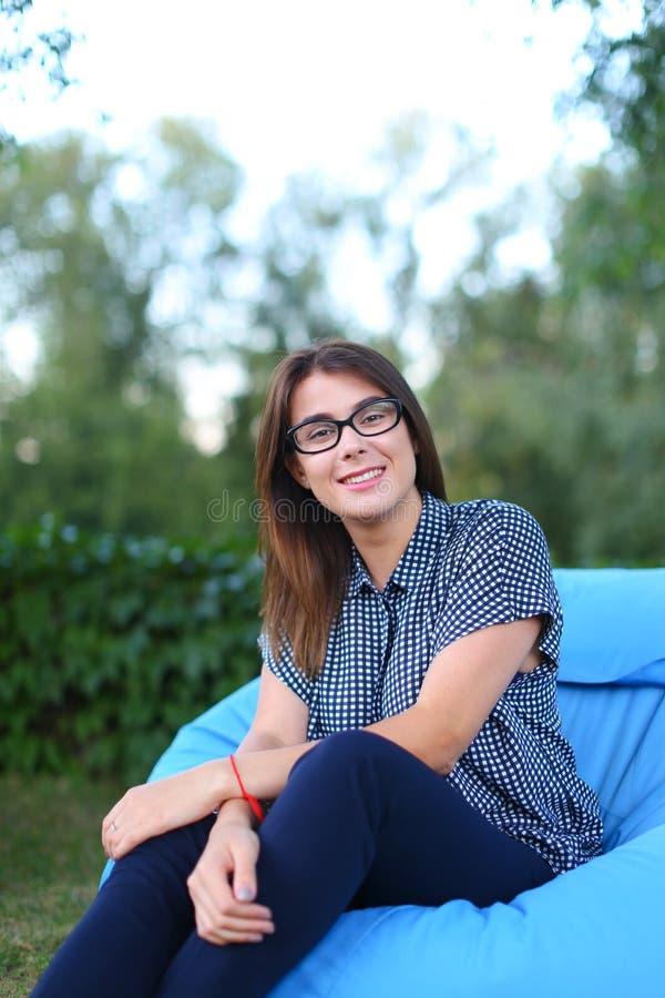 Portrait assez de femelle qui s'est reposé dans la chaise et la pose pour le photog photo stock