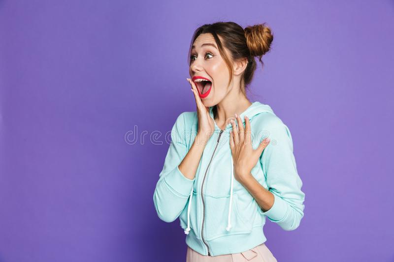 Portrait of astonished attractive woman with two buns holding ha. Nd at mouth and screaming aside isolated over violet background in studio royalty free stock photo
