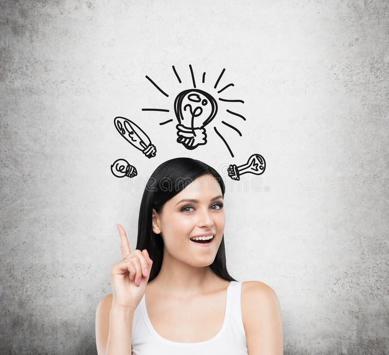 A portrait of an astonished brunette lady in a white tank top. Drawn light balbs as a concept of new ideas. Concrete background royalty free stock image