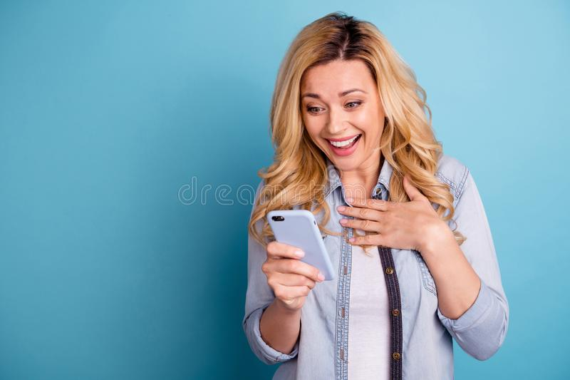 Portrait of astonished funny lady touching her chest screaming holding modern technology isolated over blue background. Portrait of astonished funny lady royalty free stock photo