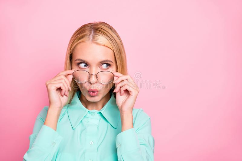 Portrait of astonished girl looking touching her specs wearing mint colored shirt isolated over pink background. Portrait of astonished girl looking, touching stock image