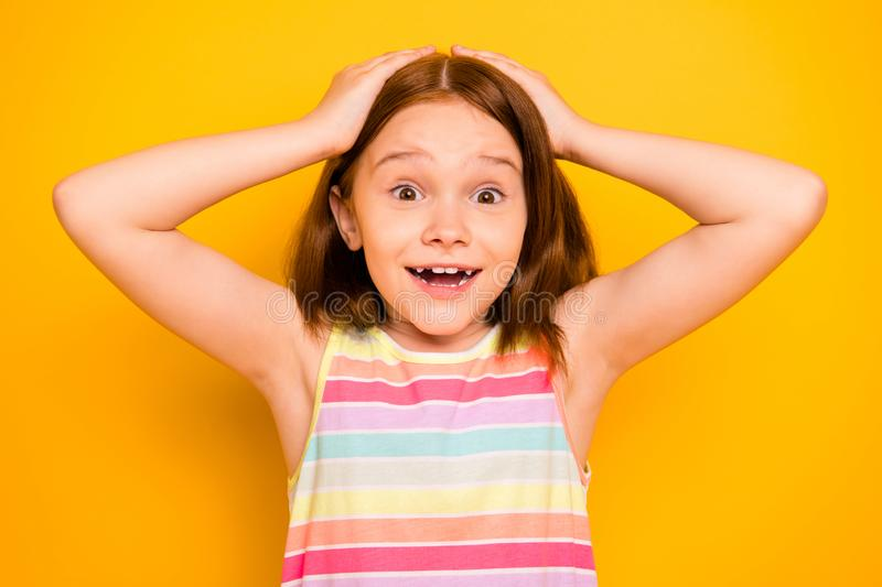 Portrait of astonished girl touching her head screaming shouting isolated over yellow background. Portrait of astonished girl, touching her head screaming stock photos