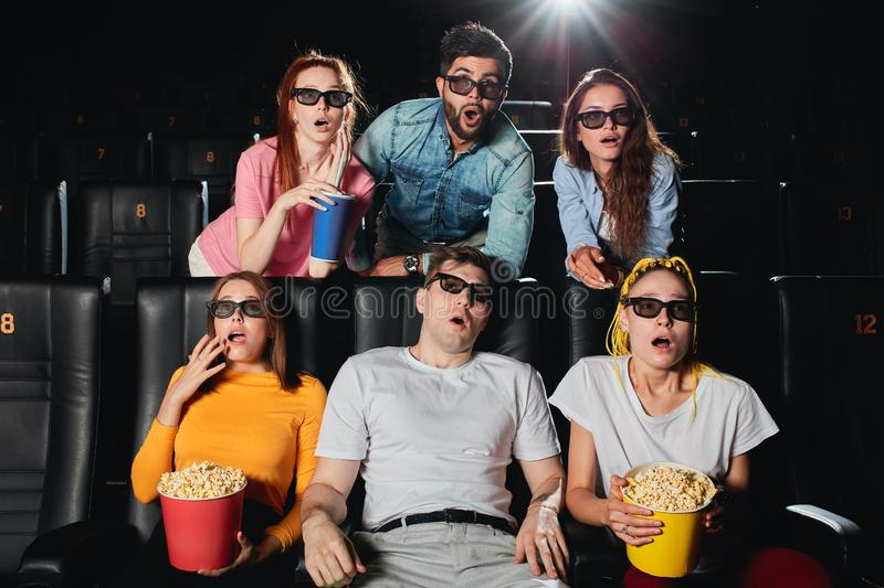 Portrait of an astonished group of young people staring at the screen. At the cinema. close up photo stock images