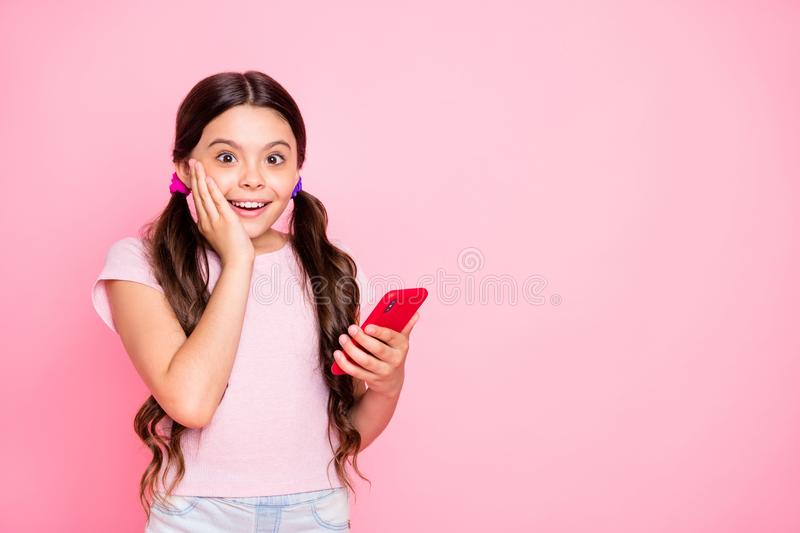 Portrait of astonished kid holding device screaming touch cheek with hand wear white t-shirt  over pink. Portrait of astonished kid holding, device screaming stock images