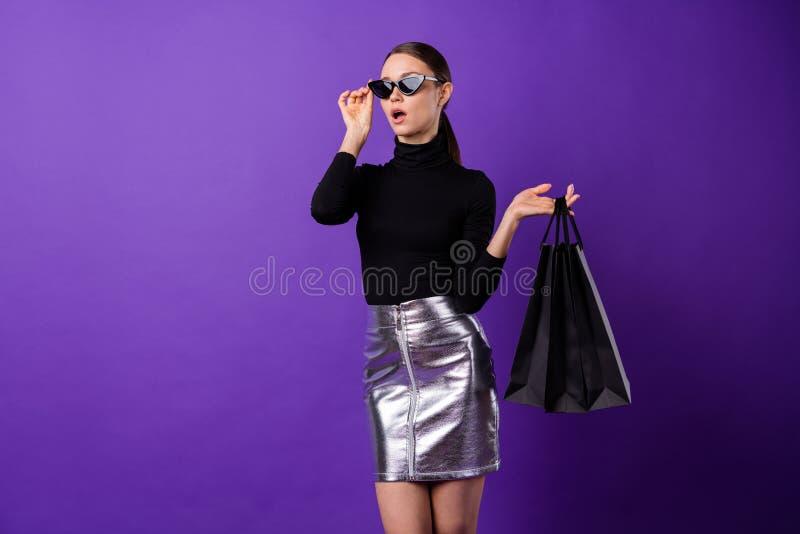 Portrait of astonished lady touching her eyewear eyeglasses holding bags staring isolated over purple violet background. Portrait of astonished, lady touching royalty free stock photo