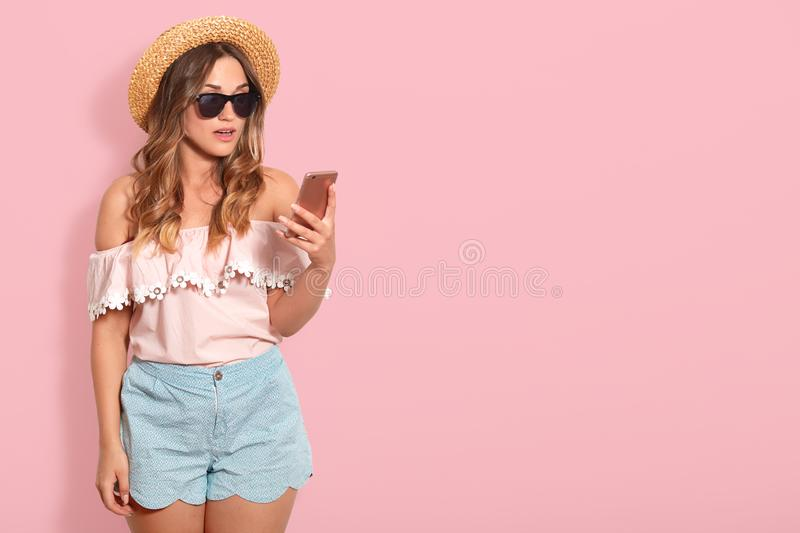 Portrait of astonished pretty woman wearing blouse with bared shoulders, short, straw hat and sunglasses, holds smart phone with royalty free stock images