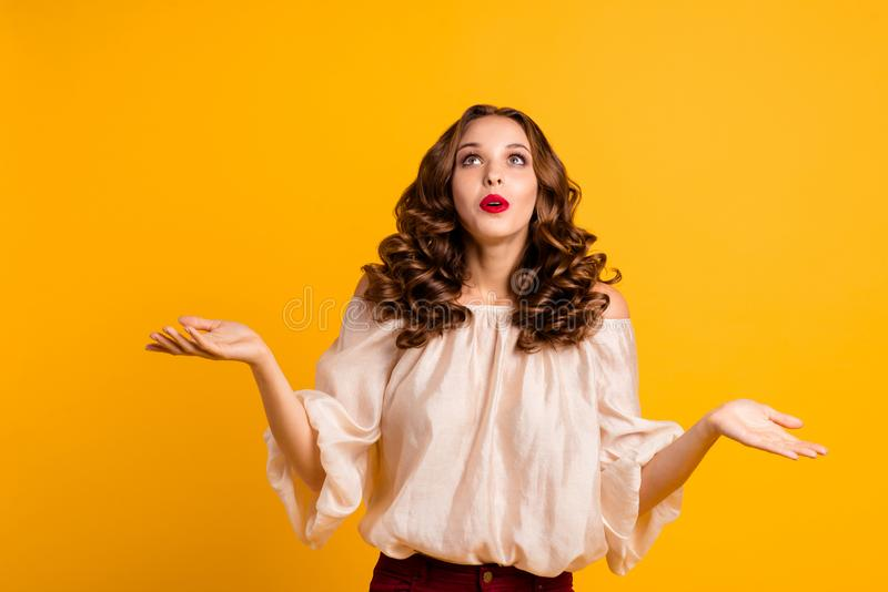 Portrait of astonished worried teen teenager impressed by unbelievable news dont know cant solve decide choose shrug. Shoulders  on yellow background dressed in royalty free stock photo