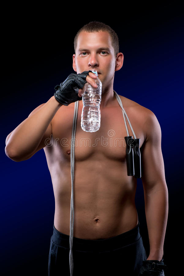 Portrait of an athlete with a skipping rope and a bottle. Of water on a black background royalty free stock images
