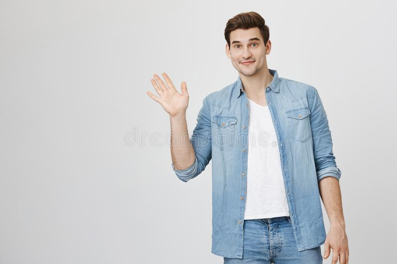 Portrait of athletic handsome man waving and looking friendly at camera while standing over white background. Cute stock photo