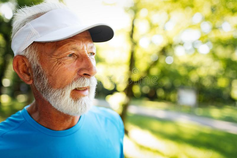 Portrait of athletic mature man after run. Handsome senior man resting after jog at the park. On a sunny day royalty free stock images