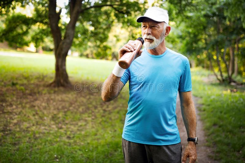 Portrait of athletic mature man after run. Handsome senior man resting after jog at the park stock photography