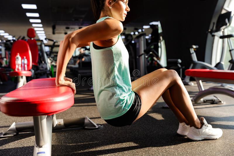 Portrait of athletic sporty woman in tracksuit doing sit-ups, wh. Portrait of athletic sporty woman in tracksuit doing sit-ups while working out in gym stock photography