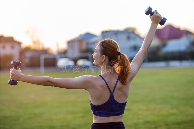 Portrait of athletic teenage girl in fitness wear exercising with blue dumbbells outdoors in park. Fit young woman working out stock image