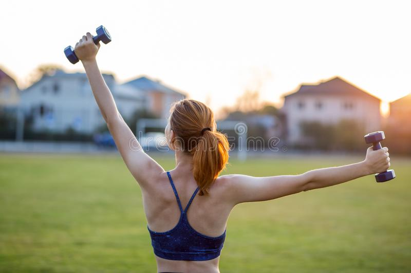 Portrait of athletic teenage girl in fitness wear exercising with blue dumbbells outdoors in park. Fit young woman working out. Outside royalty free stock image