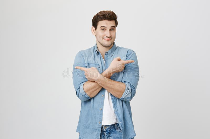 Portrait of athletic young guy being uncertain, shrugging shoulders and pointing in different directions, standing over. Gray background. Man is not sure where royalty free stock photo
