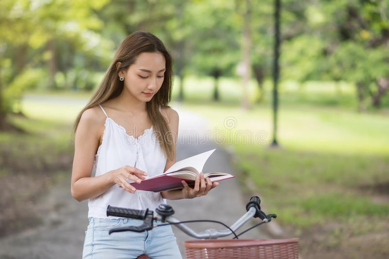 Beautiful girl read book and sit on bicycle royalty free stock photo