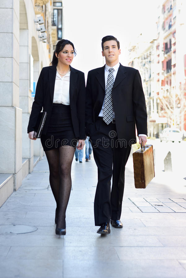 Attractive business people walking on the street. Couple working royalty free stock photography