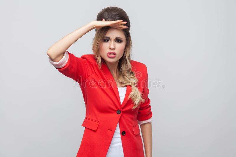 Portrait of attentive beautiful business lady with hairstyle and makeup in red fancy blazer, standing holding hand on forhead and. Looking far. indoor studio royalty free stock image