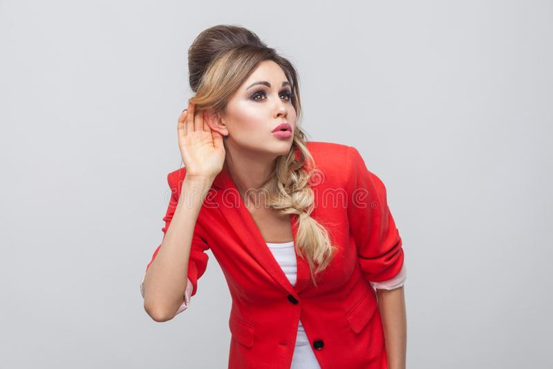 Portrait of attentive beautiful business lady with hairstyle and makeup in red fancy blazer, standing holding hand on her ear and. Trying to listen. indoor royalty free stock images