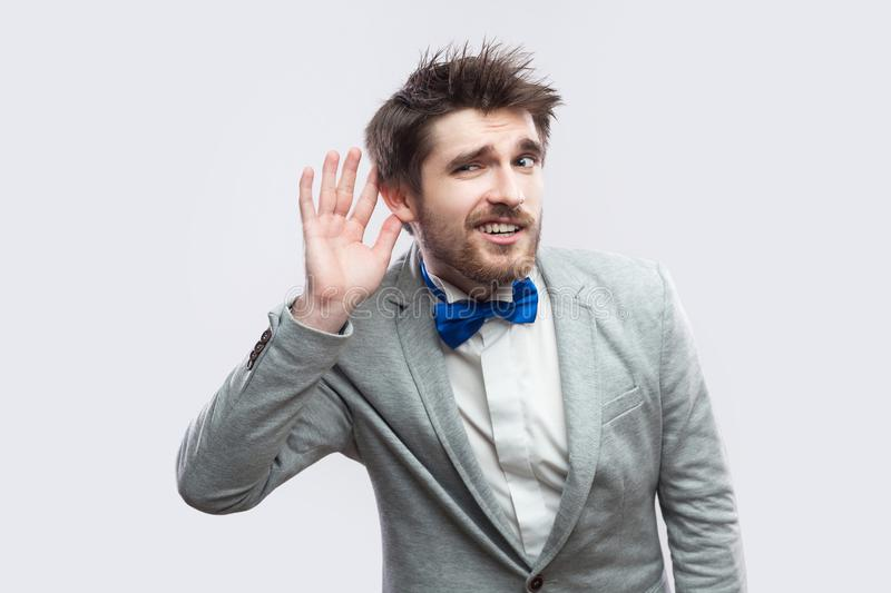 Portrait of attentive handsome bearded man in casual grey suit and blue bow tie standing holding hand near ear and trying to hear stock images