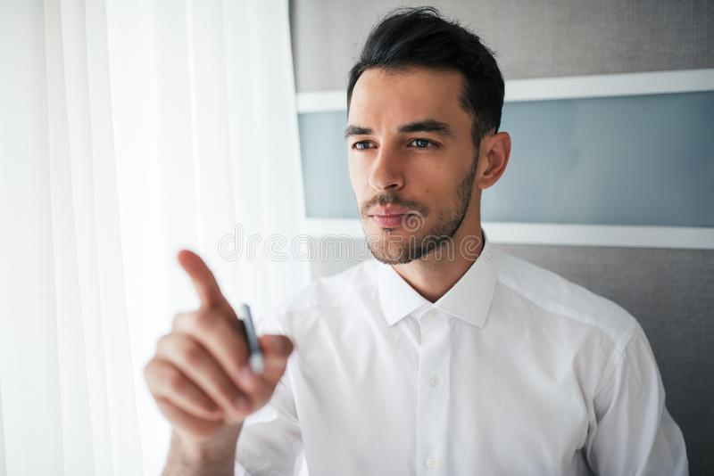Portrait of attentive handsome businessman showing or pointing with a finger in the office. stock images