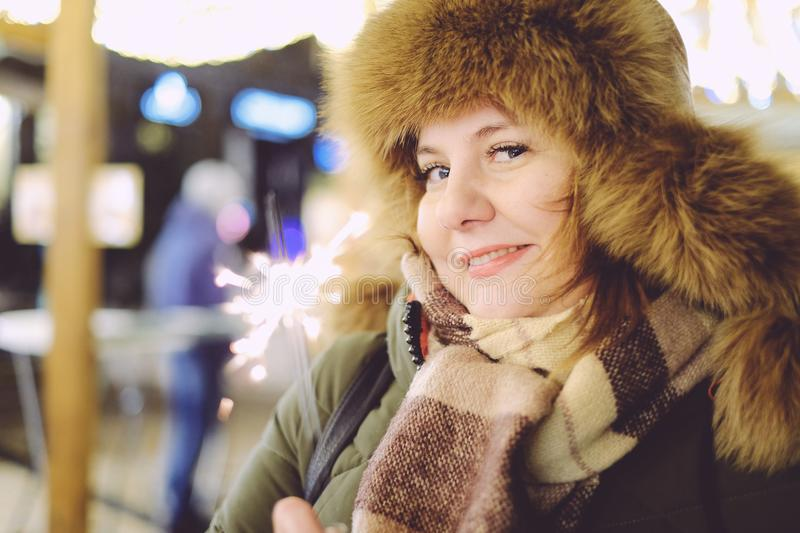 Portrait of attractive adult plus size model, smiling, winter, N. Portrait of attractive adult plus size model, winter, smiling and holding sparkler, New Year or stock image