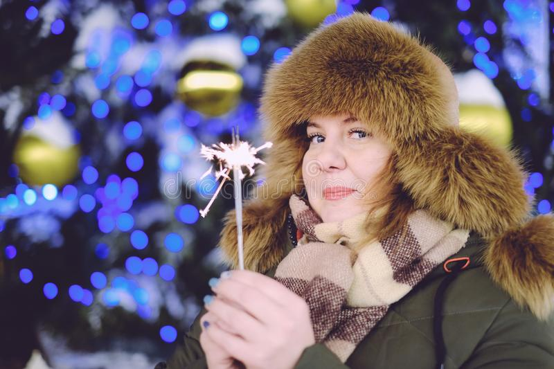 Portrait of attractive adult plus size model, smiling, winter, N. Portrait of attractive adult plus size model, winter, smiling and holding sparkler, New Year or royalty free stock photography