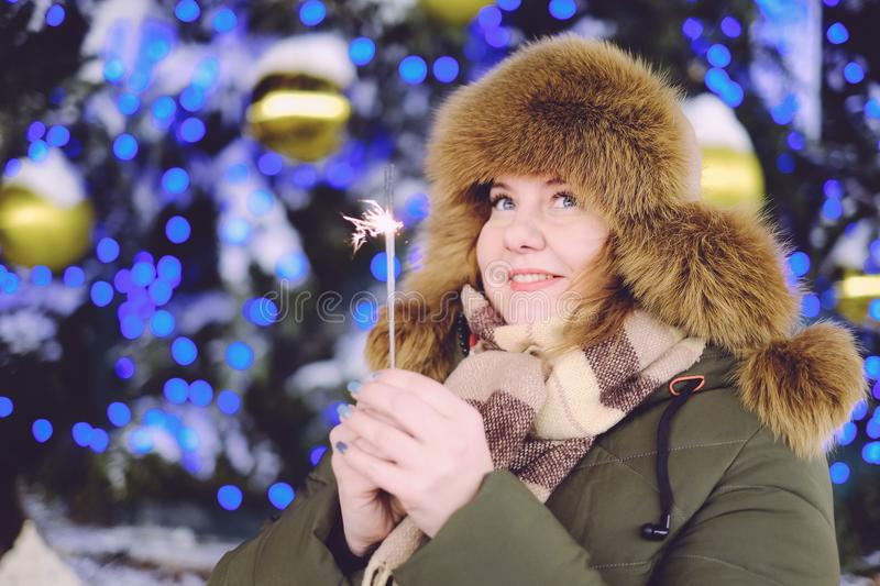 Portrait of attractive adult plus size model, smiling, winter, N. Portrait of attractive adult plus size model, winter, smiling and holding sparkler, New Year or stock photo
