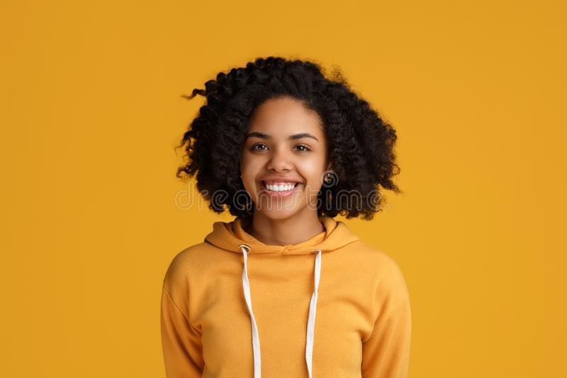 Portrait of attractive african american young woman with beautiful smile dressed in casual clothes over yellow royalty free stock images