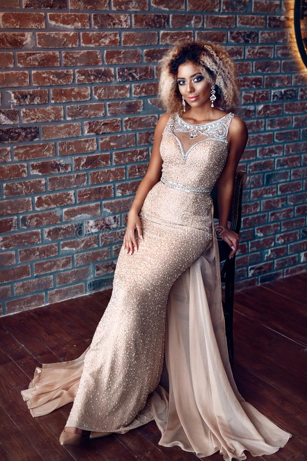Portrait of attractive afro american young woman in tight gold dress in a luxury apartment. Beauty and fashion concept stock image