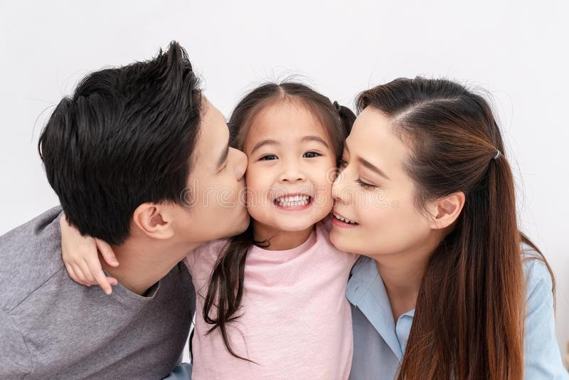 Portrait of attractive asian family kissing cheek together close up on isolated white studio background. Gen alpha and millennials. Lifestyle, parenthood or royalty free stock photography