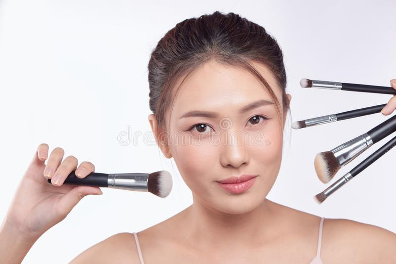 Portrait of attractive asian smiling woman brunette isolated on white studio shot with brushes for makeup.  stock photo