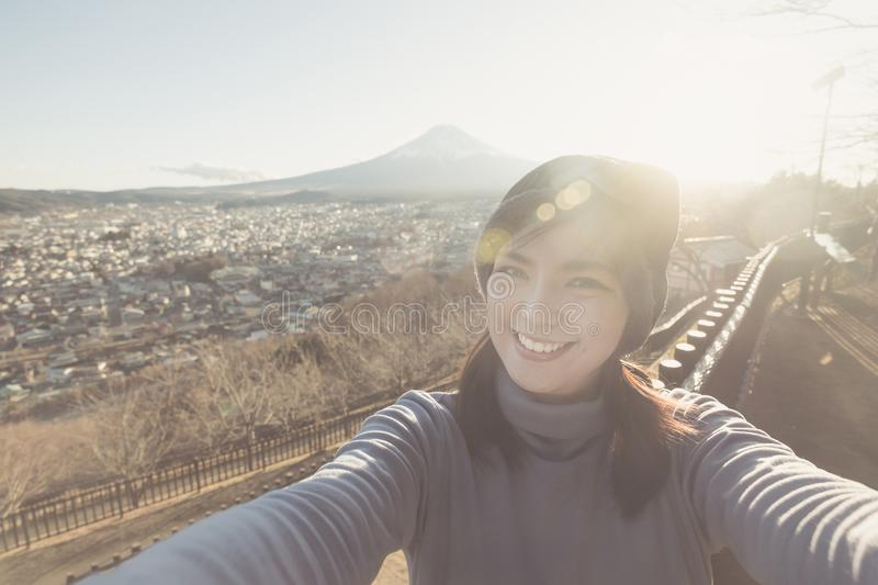 Portrait of Attractive asian woman making selfie photo with moutain Fuji background on sunset royalty free stock photo