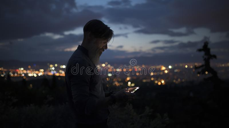 Portrait of an attractive bearded man who is on a mountain high over the city lights writing an sms royalty free stock photography