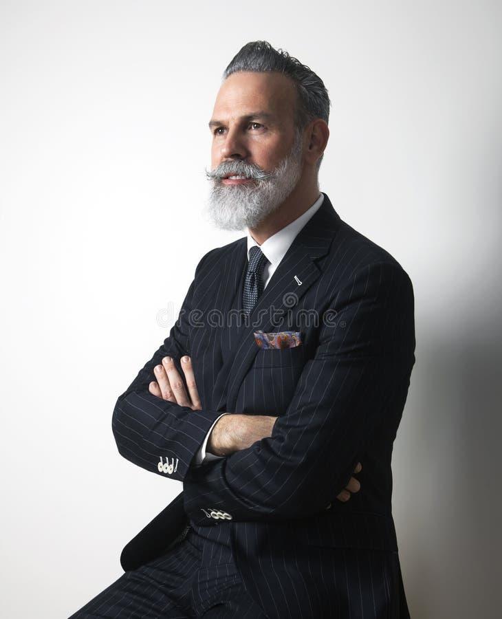 Portrait of attractive bearded middle aged gentleman wearing trendy suit over empty gray background. Studio shot stock image