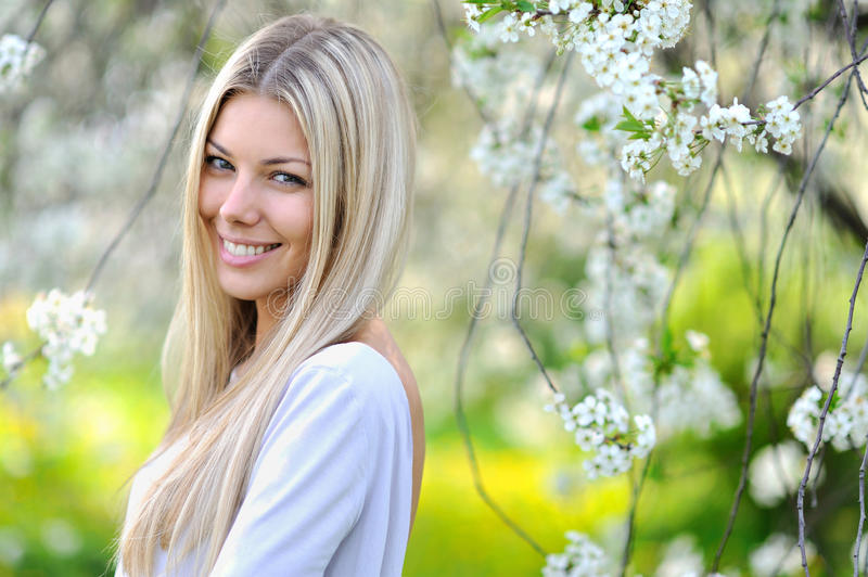 Portrait of attractive beautiful blonde woman in green blooming. Portrait of attractive beautiful blonde woman stock photo