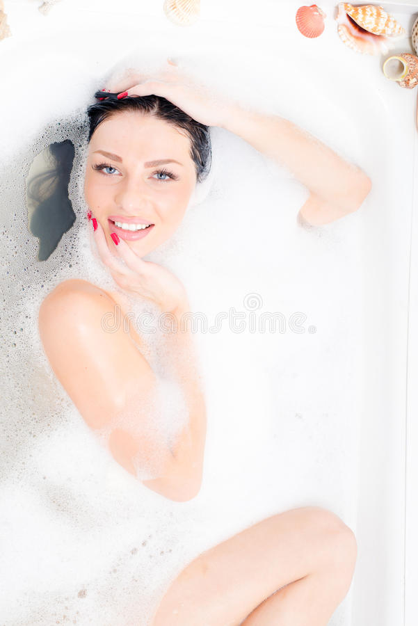 Portrait of attractive beautiful blue eyes young woman lying relaxing in the luxury bath with foam happy smiling royalty free stock photos