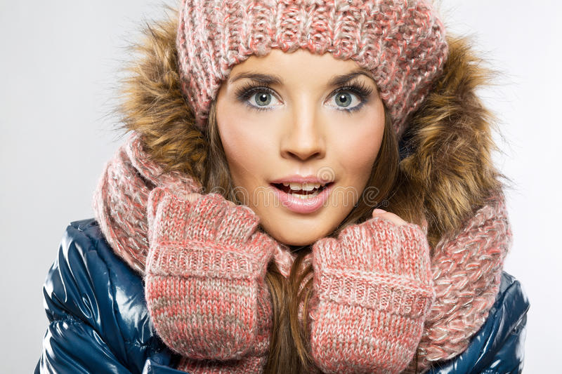 Portrait of attractive beautiful young smiling woman wearing gloves, winter cap and scarf stock image